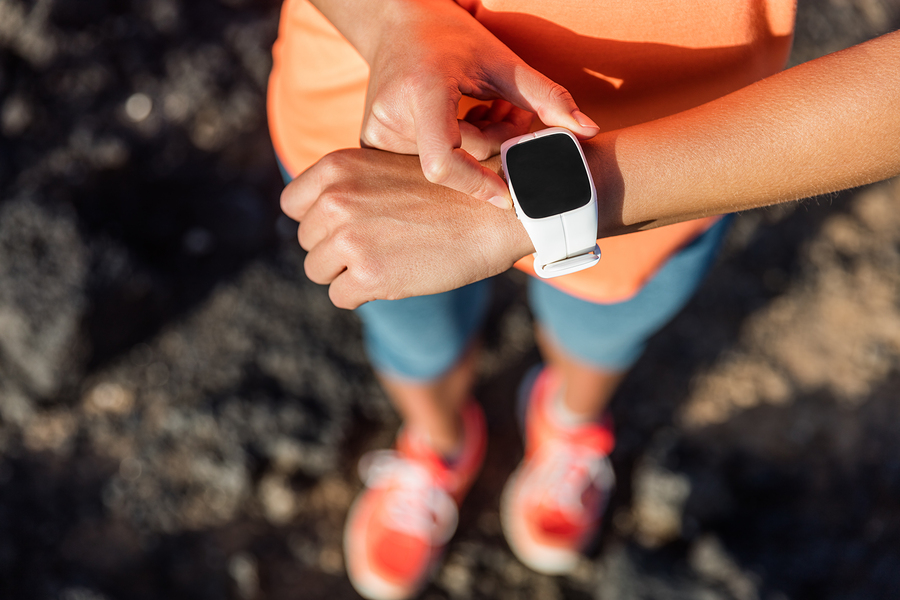 Trail runner athlete using her smart watch app to monitor fitnes